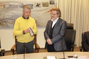 Thierry Deleu (rechts) overhandigt het jaarboek aan de schepen van Koksijde. Foto: Peter le Nobel